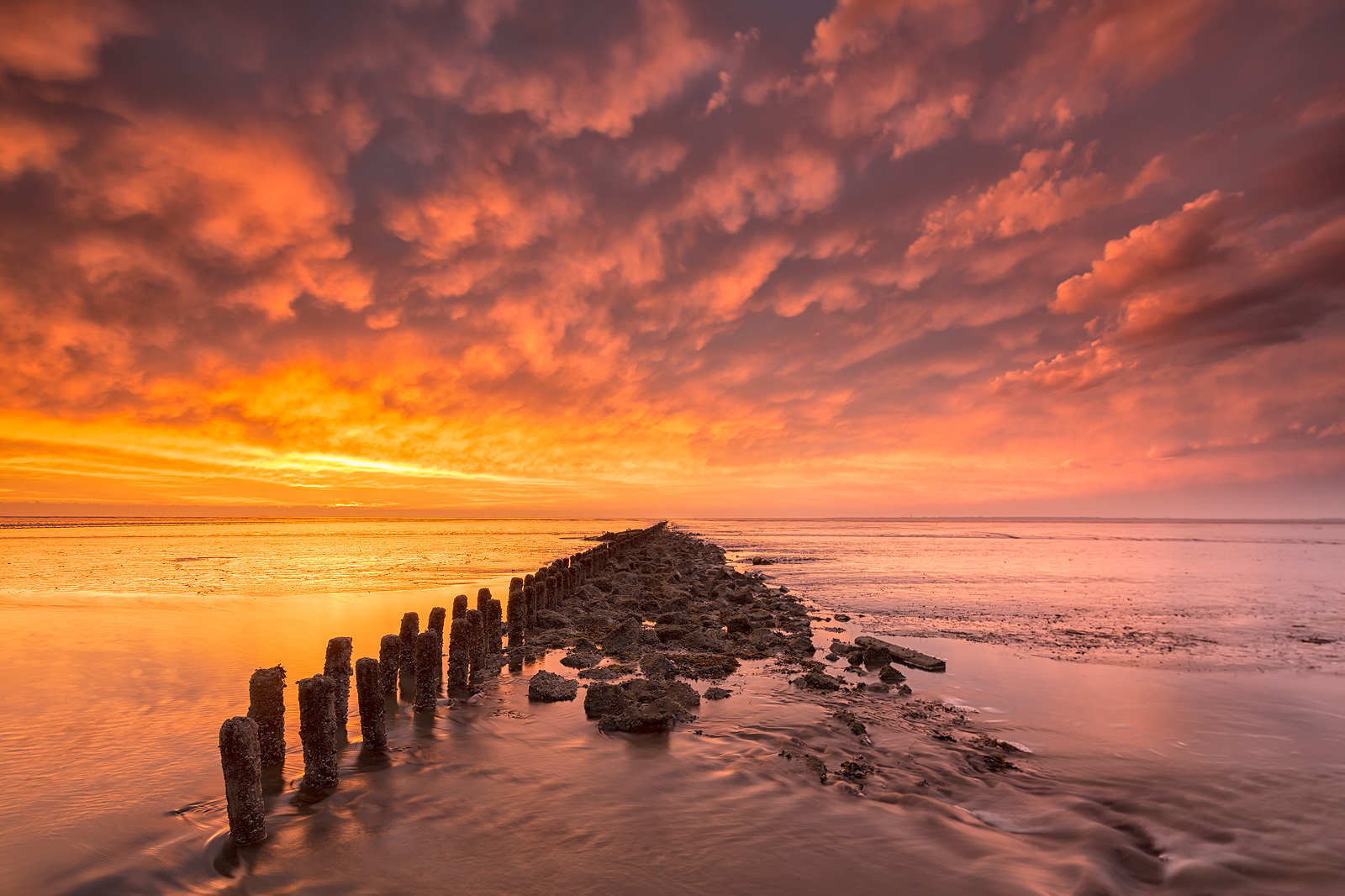 Zonsondergang boven de Waddenzee in Groningen met prachtige kleuren in de lucht.