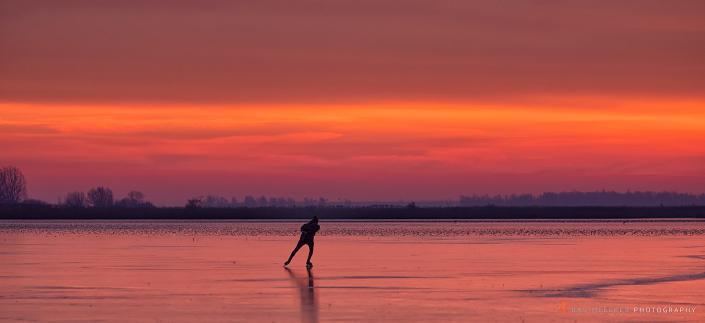 Schaatsers genieten van het eerste ijs op het Lauwersmeer tijdens de zonsopkomst - Bas Meelker Landschapsfotografie