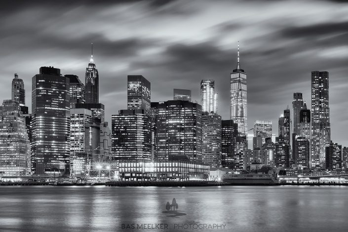 Zwart-wit foto van de skyline van Manhattan in New York, USA, in de nacht. De lichte van de wolkenkrabbers weerspiegelen in het water.