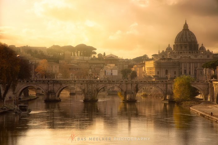 View over the Tiber in Rome with the Ponte Sant'Angelo and Saint Peters Church in the backgrpound on a sunny autumn afternoon with warm golden light - Rome, Italy