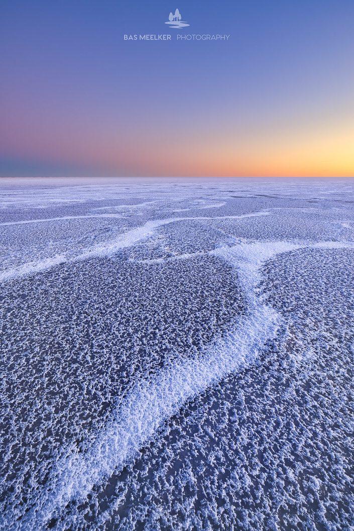 Mooie structuren op een met ijs bedekt IJsselmeer tijdens de winter. Aan de horizon komt de zon langzaam op en geeft een mooie gloed en kleuren aan de lucht.