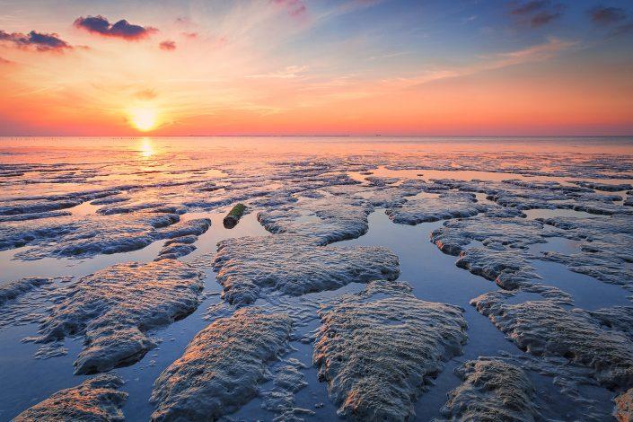 Een zomerse zonsondergang bovem de Waddenzee bij laag water