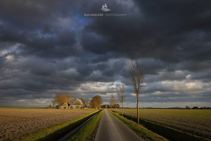 Warm winter licht verlicht het Gronings landschap op een januari dag terwijl donkere stormwolken voorbij trekken. Temidden van de lege akkers staat een eenzame boerderij in het vlakke landschap van Groningen.