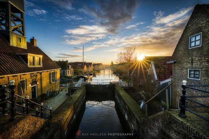 De laatste zonnestralen van de dag vallen op de Friese stad Hindeloopen. Warm licht valt op de huizen en geeft een mooie sfeer aan de foto.