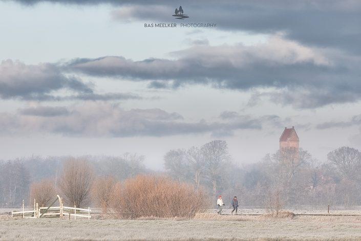 Wandelaars genieten van een koude winter ochtend op Landgoed Nienoord bij Leek met op de achtergrond de toren van het kerkje in Midwolde