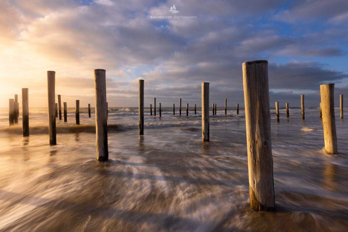 Zonsondergang op het strand bij Petten. De koude noordenwind drijft mooie wolkenluchten voorbij terwijl de golven op het strand slaan.
