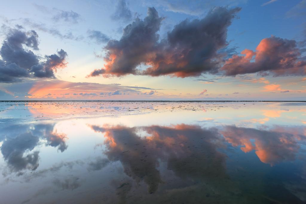 Een mooie zonsondergang boven de Waddenzee met reflecties op het water