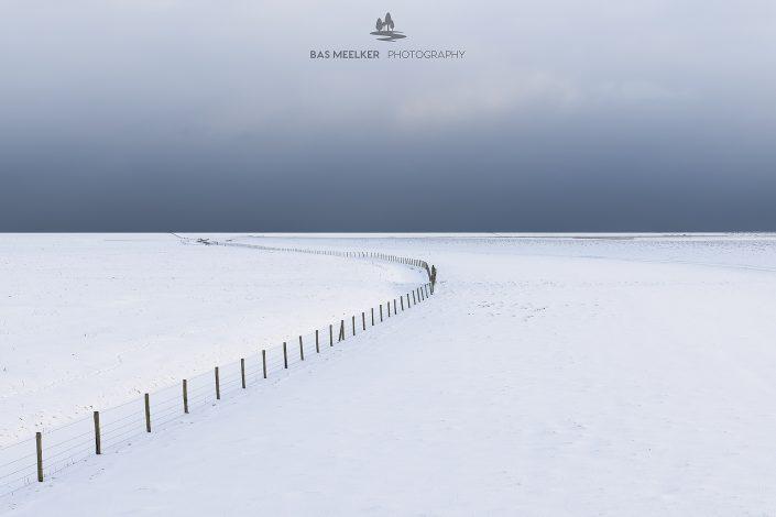 Een leeg winters landschap bedekt met sneeuw in het Nationaal park Lauwersmeer. Aan de horizon drijven donkere sneeuwwolken binnen en geven het landschap een dreigende sfeer. Een minimalistische foto.