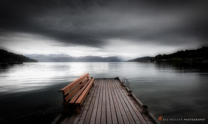 A dramatic mystical landscape in black and white with a jetty and a bench with mountains in the background and reflections on the water