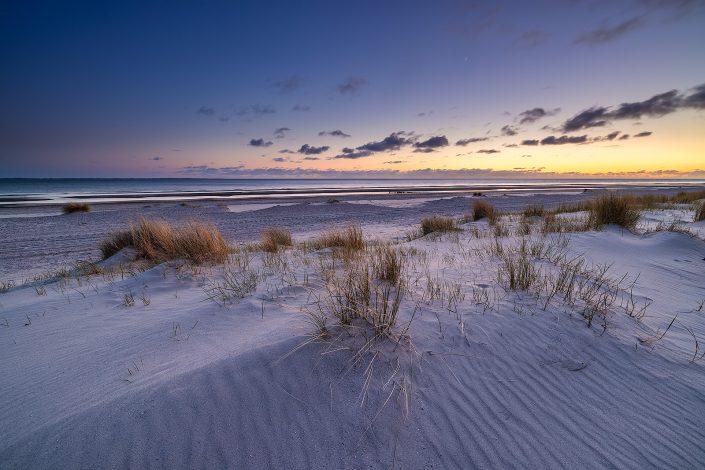 Zonsondergang op het strand bij Westerschouwen op Schouwen-Duivenland in Zeeland. Het laatste licht van de dag weerspiegelt op de duinen. Een sfeervol landschap.