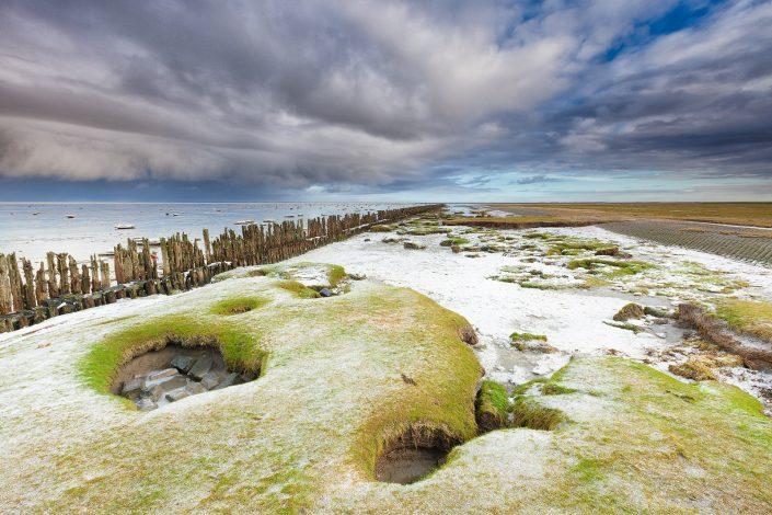 Winter bij de Waddenzee met donkere sneeuwwolken die boven de waddenzee drijven.