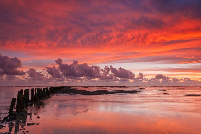 Een spectaculaire avondrode zonsondergang boven de Waddenzee bij ternaard in Friesland.