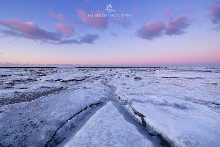 IJs bedekt de Waddenzee in de winter aan de Groningse Waddenkust tijdens zonsondergang. De ondergaande zon geeft een mooi gloed en kleuren aan de lucht.