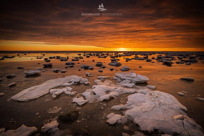 De Waddenzee is bedekt met IJsschotsen in de winter. Een mooie zonsondergang geeft prachtige kleuren in de lucht en de laatste zonnestralen geven het landschap een warme gloed.