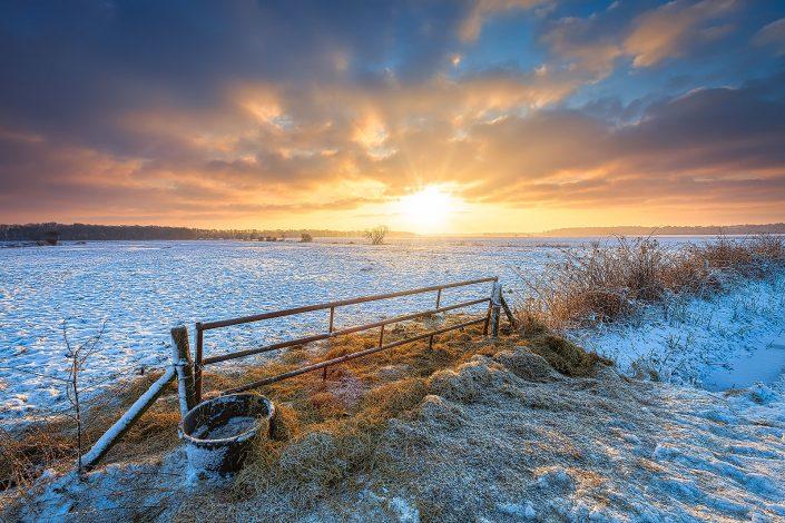 Winter in Drenthe met een mooie zonsopkomst en sneeuw over de weilanden. Op de voorgrond een hek met vers hooi voor het vee.