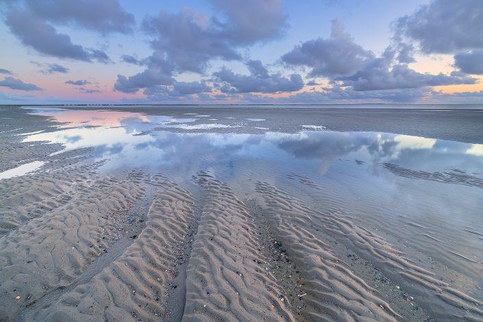 Eb op het strand van Westerschouwen op Schouwen-Duivenland in Zeeland. De wolken weerspiegelen in het water op het strand tijdens zonsondergang.
