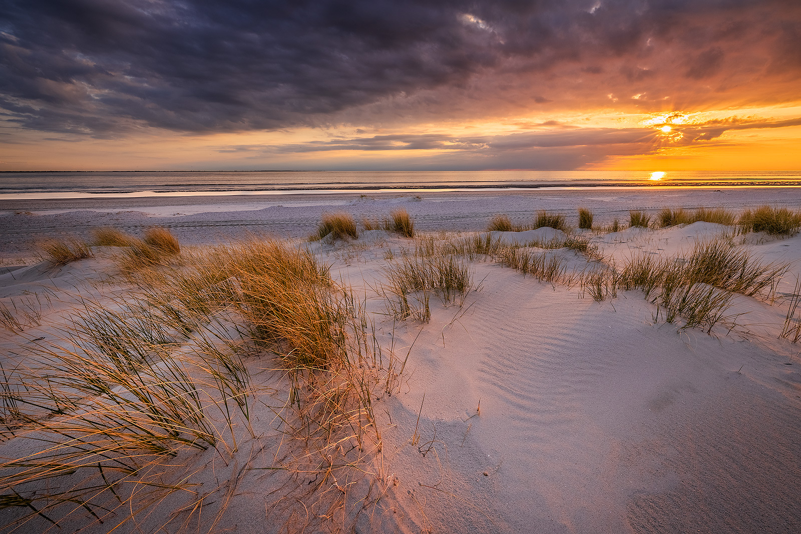 Zonsondergang op het strand van Westerschouwen op Schouwen-Duivenland in Zeeland met duinen op de voorgrond. Avondrood kleurt de lucht en geeft het landschap een prachtige sfeer.