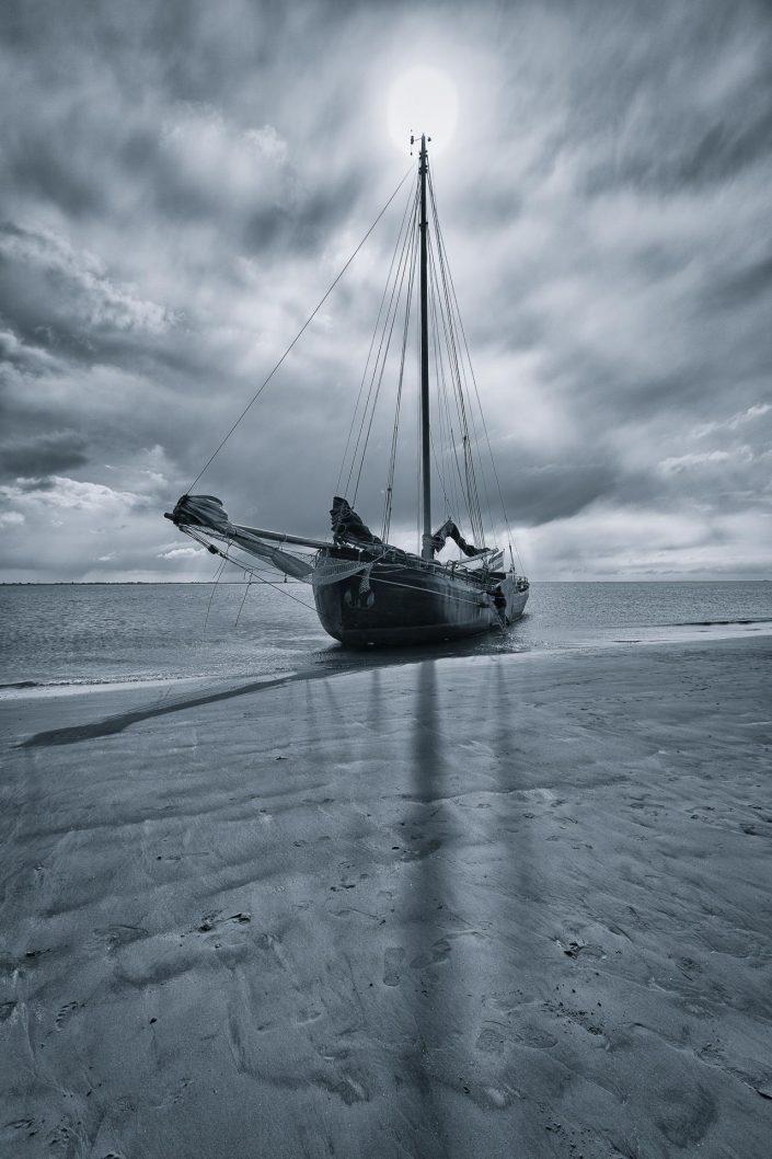 Zwart wit opname van een drooggevallen schip op het Wad