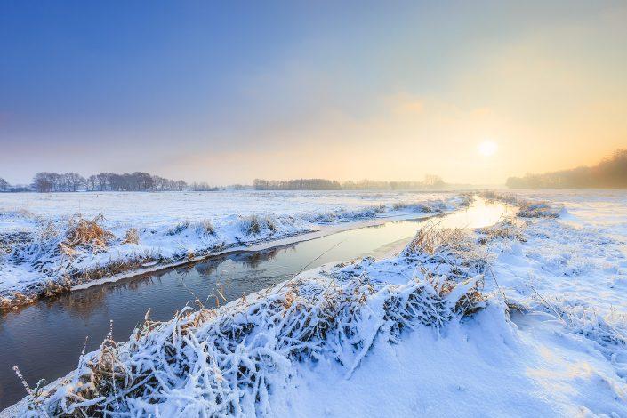 Winter landschap bij het Oostervoortsche diep bij Norg in Drenthe tijdens zonsopkomst. De zon komt op in een mistig wit landschap waar de beek doorheen stroomt.