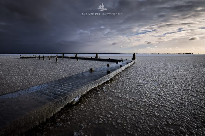 Een koude zonsopkomst in de winter boven het Lauwersmeer. Het water is bevroren en de stijger bedekt met ijs. Vanuit het noorden drijven donkere sneeuwwolken binnen.