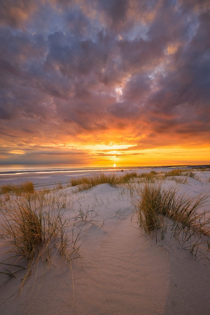 Een prachtige zonsondergang op het strand bij Westerschouwen op Schouwen-Duivenland in Zeeland. Het laatste warme avondlicht valt op de duinen op de voorgrond.