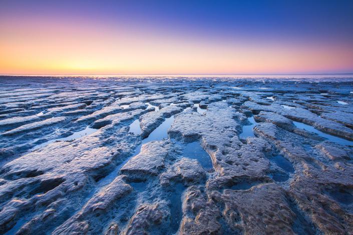 Zonsondergang boven de Waddenzee bij eb. Er hangt een prachtige gloed in de lucht met mooie kleuren die reflecteren op de mudflats.