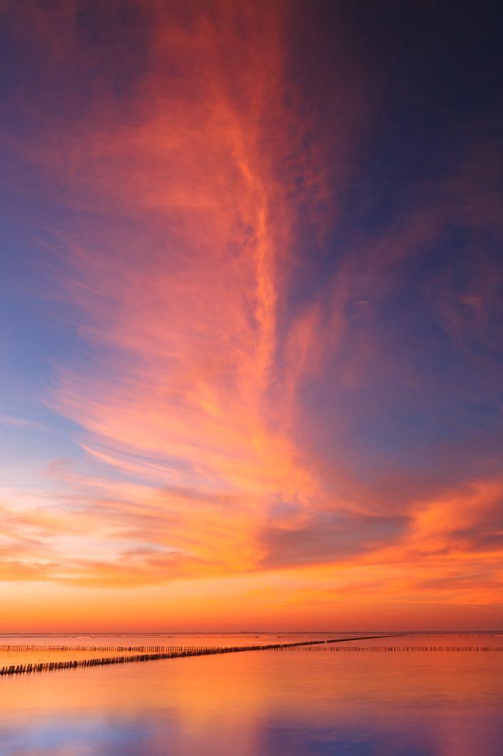 Zonsondergang boven de Waddenzee met een mooie avondrode lucht