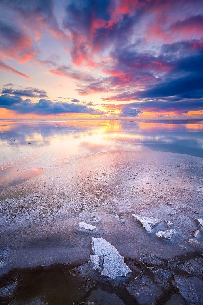 Winter landschap op het IJsselmeer bij Workum in Friesland met een kleurrijke zonsondergang.