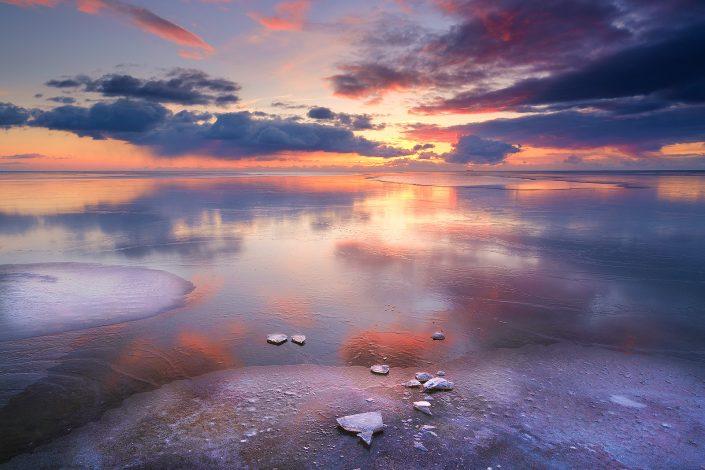 Winter landschap op het IJsselmeer bij Workum in Friesland met een kleurrijke zonsondergang. Wolken drijven voorbij tijdens de zonsondergang en zorgen voor een winterse sfeer.