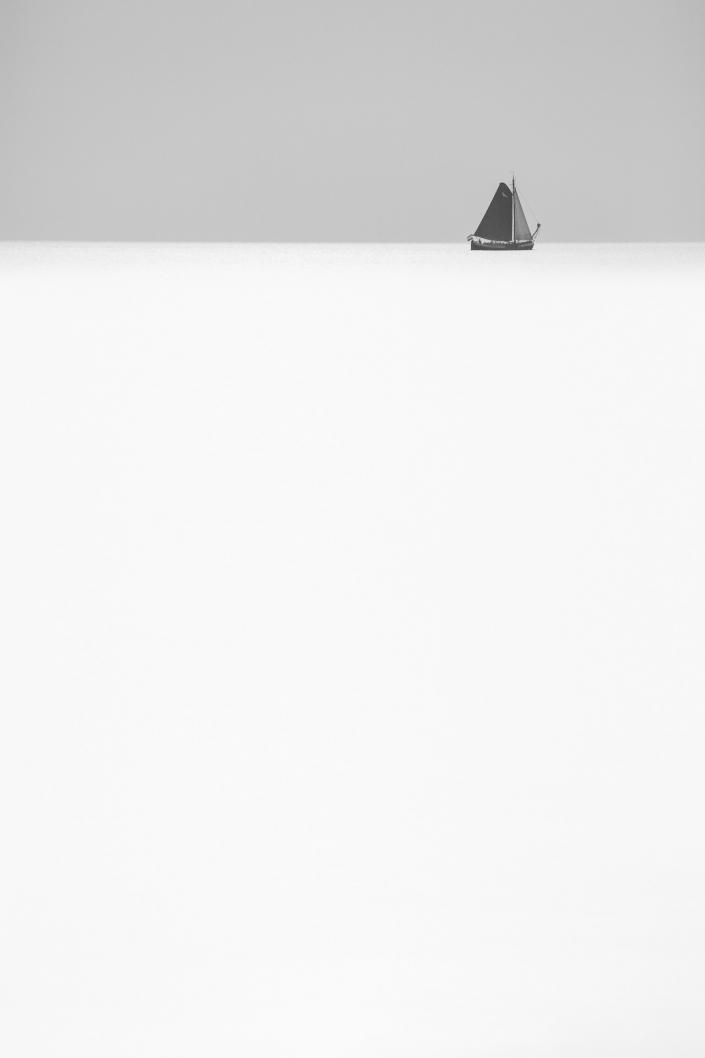 Zwart-wit abstracte foto van een zeilschip aan de horizon op zee. Een sfeervolle foto om bij weg te dromen. De foto op genomen op een rustige en kalme avond in de zomer.